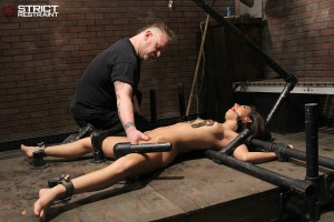 Slave bound in steel and nipple clamped